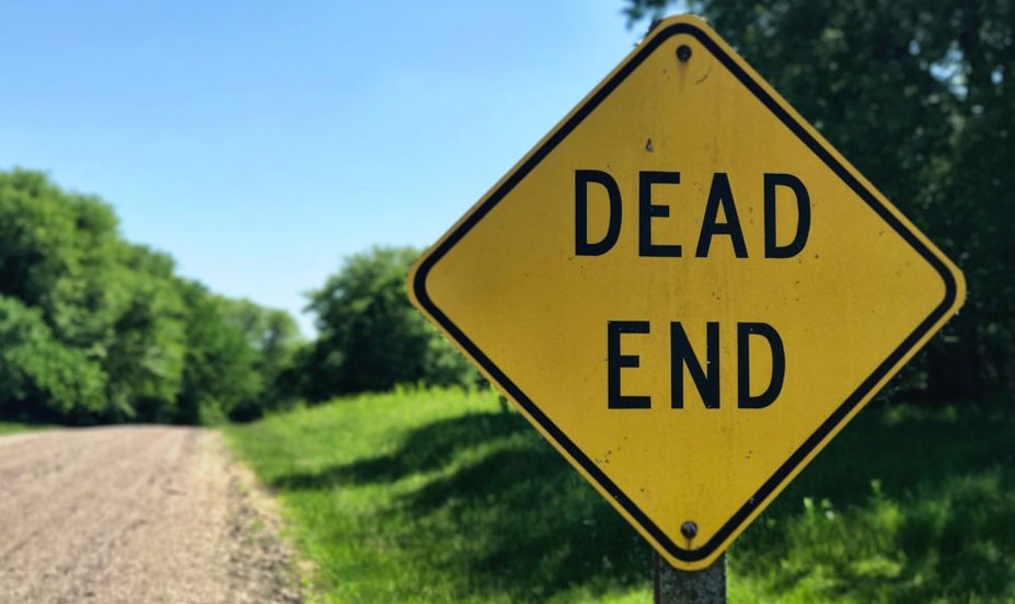 A Dead End road sign in front of a dirt road. This symbolizes the end of life for Magento 1, which took place on June 30th, 2020.